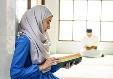 Muslim woman reading from the Quran royalty free stock images