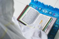 Muslim woman reading Quran with pointer stick Royalty Free Stock Image