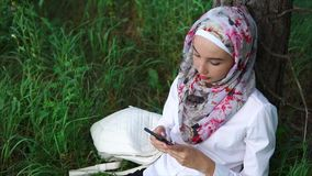Muslim woman relaxing outdoor and using cellphone stock video