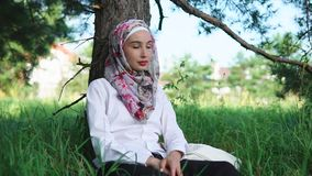 Muslim woman relaxing in the park stock video footage