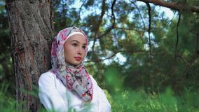 Muslim woman relaxing in the park. Young Muslim woman relaxing in city green park. She sitting on the grass leaning on the tree stock video