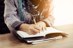 Muslim woman hand with writing some note onto anotebook by pen in the morning stock photos