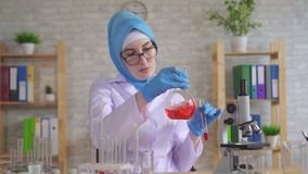 Muslim woman scientist chemist in national scarf working in the lab close up slow mo. Muslim woman scientist chemist in glasses in national scarf working in the stock video