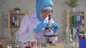 Muslim woman scientist chemist in national scarf working in the lab. Muslim woman scientist chemist in national scarf in glasses working in the lab stock video
