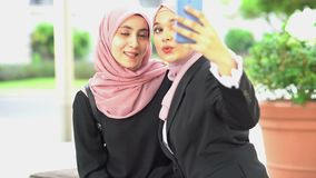 Muslim woman selfie. Muslim woman taking self photo, using smartphone camera stock video footage