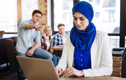 Muslim woman sitting in the cafe. She differs. PLeasant beautiful muslim woamn sitting at the table and using laptop while other people humiliating her stock photography
