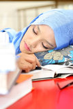 Muslim woman sleeping at the table. A young muslim woman sleeping while reading a book Royalty Free Stock Images