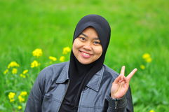 A muslim woman smiles in spring season. A muslim woman with head scarf smiles while giving a peace symbol when posing for photo. The picture is taken in early Royalty Free Stock Image
