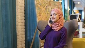 Muslim woman smiling talking on a cell phone stock video