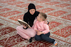 Muslim woman and son reading Koran, muslim family Stock Photos
