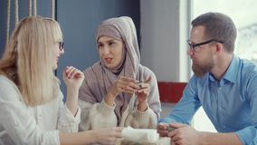 Muslim woman is speaking stories to her male and female friends in cafe stock footage