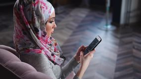 Muslim woman spending leisure with mobile at home. Young Muslim woman relaxing on the sofa at home and using cellphone to surf the internet. Lifestyle and stock video footage