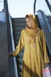 Muslim Woman Standing On Escalator. Happy Muslim woman in traditional wear standing on escalator with shopping bags Stock Photography