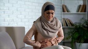 Muslim woman suffering abdominal pain, period cramp, needs medical aid. Stock photo stock photo
