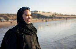 Muslim woman on the sunny beach. Portrait at sunset Stock Photos