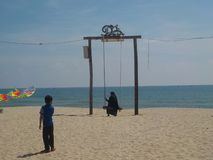 Muslim woman on a swing looking at the sea and her child with colorful kite. royalty free stock photos