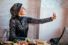 Muslim woman taking selfie in cafe with smartphone Royalty Free Stock Image