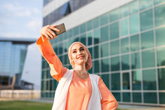 Muslim woman taking selfie. Girl in abaya on the background of the business center Royalty Free Stock Photography