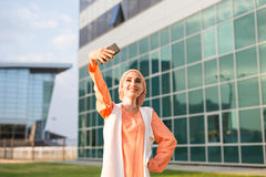 Muslim woman taking selfie. Girl in abaya on the background of the business center Royalty Free Stock Photos