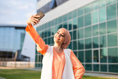 Muslim woman taking selfie. Girl in abaya on the background of the business center Stock Photos