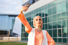 Muslim woman taking selfie. Girl in abaya on the background of the business center Stock Images