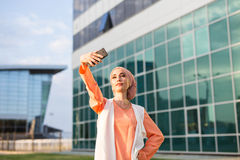 Muslim woman taking selfie. Girl in abaya on the background of the business center Royalty Free Stock Images