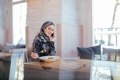 Young muslim woman talking on phone in cafe and looking on window. Muslim Woman Talking on Mobile Phone in Cafe Royalty Free Stock Photo