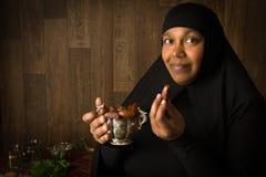 Muslim woman tasting dates stock photos