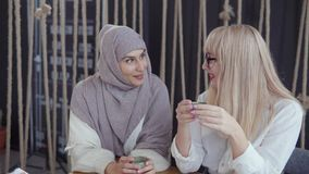 Arabian woman is talking secret to her blonde female friend during drinking tea stock video