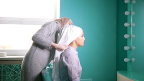A Muslim woman tying the hijab for muslim bride. A Muslim woman in front of a mirror tying the hijab for muslim bride stock footage
