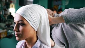Muslim woman tying Islamic turban for attractive bride. Close up stock video footage