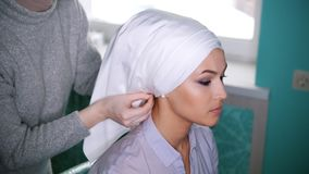 Muslim woman tying Islamic turban for attractive bride. Close up stock footage