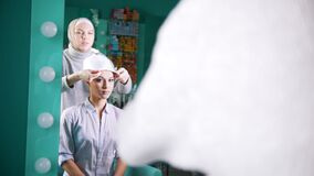 A Muslim woman tying the turban for beautiful model. A Muslim woman in front of a mirror tying the turban for beautiful model stock footage