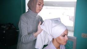 A Muslim woman tying the turban for beautiful model. A Muslim woman in front of a mirror tying the turban for beautiful model stock video footage
