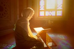Muslim woman under the sunlight. Young muslim woman reading Quran in the mosque and sunlight falling from the window Royalty Free Stock Image