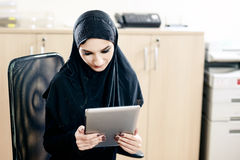 Muslim woman uses tablet while working in the office Royalty Free Stock Photography
