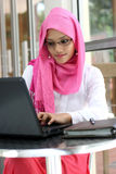 Muslim woman using laptop. A young muslim woman using laptop stock photo