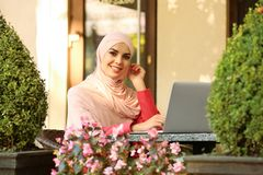 Muslim woman using laptop. In outdoor cafe stock photos