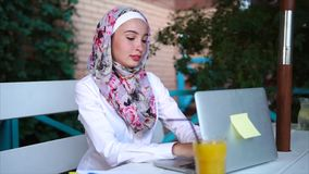 Muslim woman using laptop in outdoor cafe stock video footage