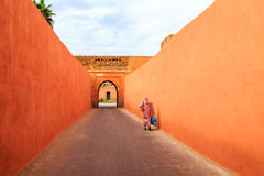Muslim woman walking through a narrow street with gate in Marrak. Muslim woman walking through a colorful narrow street with gate in Marrakech Royalty Free Stock Photography