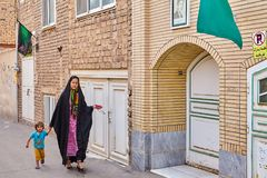 Muslim woman walks with her child along street, Kashan, Iran. Kashan, Iran - April 27, 2017: One young Muslim woman, in a black chador, thrown over a color Royalty Free Stock Photo