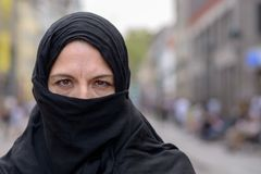Muslim woman wearing a black hijab in town royalty free stock photos