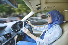 Muslim woman driving a car with fast motion. Muslim woman wearing glasses while driving a car along road with fast motion Stock Photos