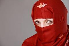 Muslim woman wearing Hijab. Muslim woman wearing red Hijab, revealing eyes Royalty Free Stock Image