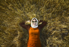 Muslim woman wearing hijab relaxing on savanna Stock Image