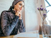 Muslim woman working in cafe. Muslim woman wearing red scarf writing beside notebook at cafe Stock Images