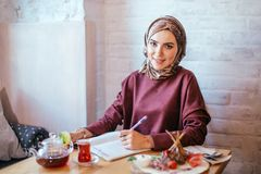 Muslim woman working in cafe. Muslim woman wearing red scarf writing beside notebook at cafe Royalty Free Stock Image