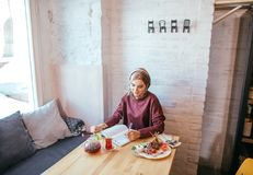 Muslim woman working in cafe. Muslim woman wearing red scarf writing beside notebook at cafe Royalty Free Stock Images
