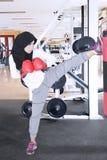 Muslim woman kicking a boxing sack stock photo