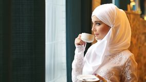 Muslim woman in a white wedding dress with a cup of tea in his hands stock video